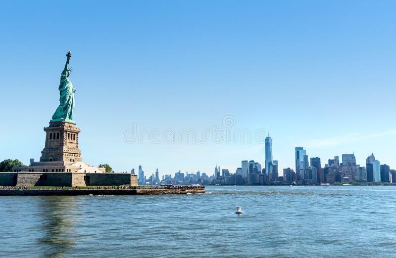 与曼哈顿地平线的自由女神像在纽约 对NYC街市的全景视图  观光在自由岛的游人 图库摄影