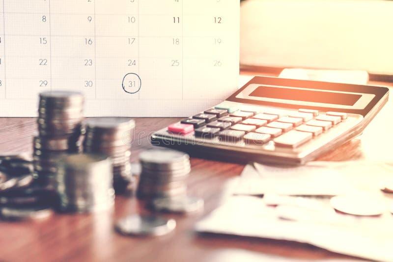 与最后期限日历的收债和税季节概念提醒笔记,硬币,银行,在桌上的计算器 免版税库存图片