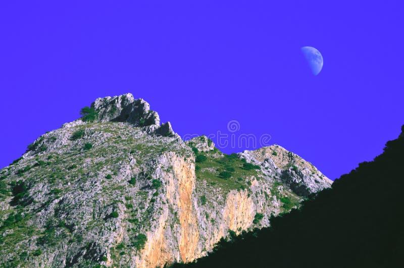 与月亮和天空蔚蓝的多山峰顶 免版税图库摄影
