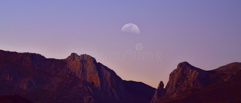 与月亮的多山天际 免版税图库摄影