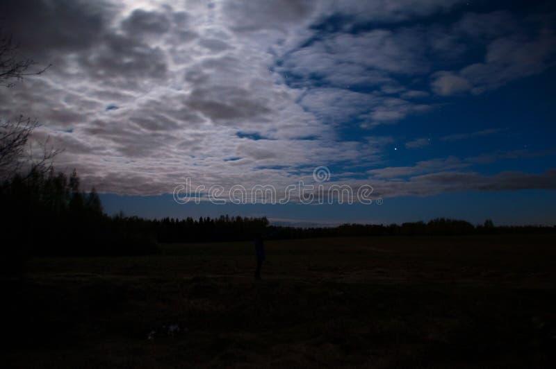 与月亮的蓝色夜在云彩下 免版税库存图片