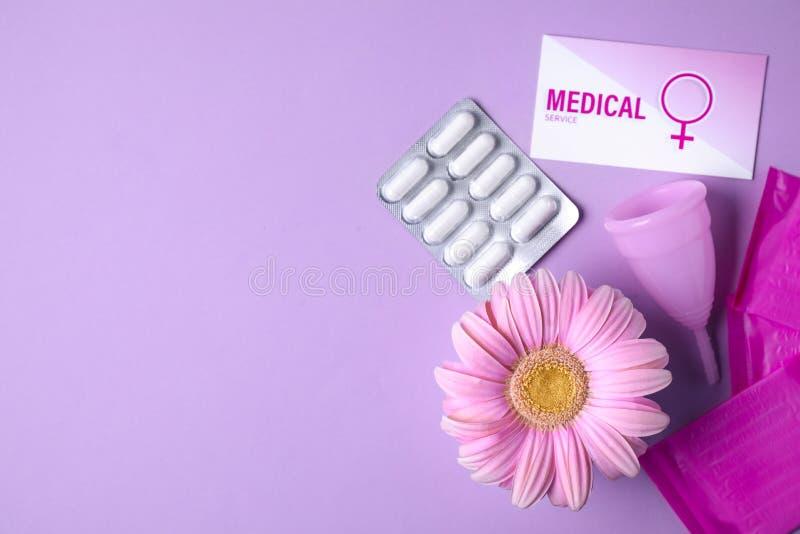 与月经杯子、药片和大丁草花的平的被放置的构成在颜色背景,文本的空间 免版税库存照片