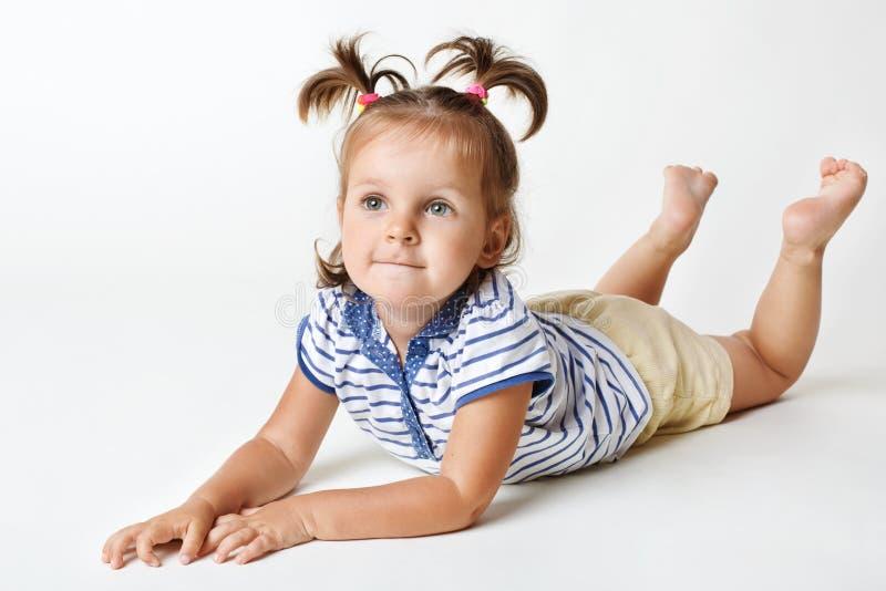 与有吸引力的神色,梦想的表示的可爱的矮小的女性孩子,有两滑稽的马尾,向上举腿,集中于一些 图库摄影