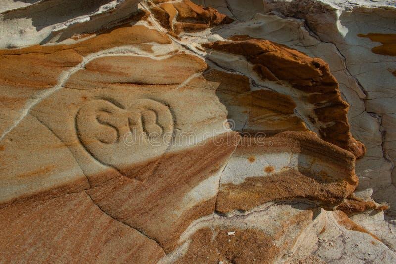 与有趣的样式和颜色的岩石露头和心脏被雕刻入岩石 免版税库存图片