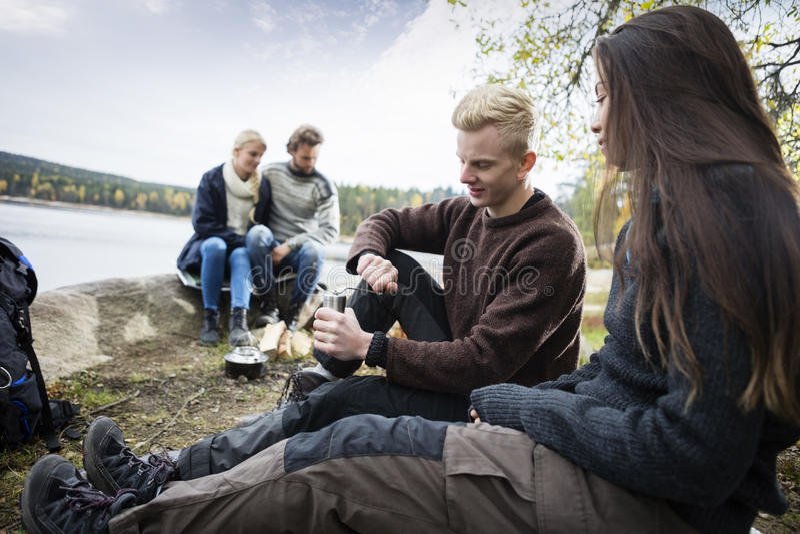 与朋友的夫妇研的咖啡在野营期间 免版税库存图片