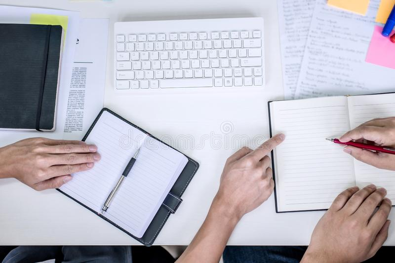 与朋友的家庭教师书,人有书的开会指向一起学习有同学检查的书桌,手或课本 免版税库存图片