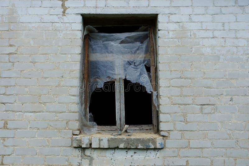 与木制框架的老空的窗口在一个被放弃的房子的一个灰色砖墙上 库存照片