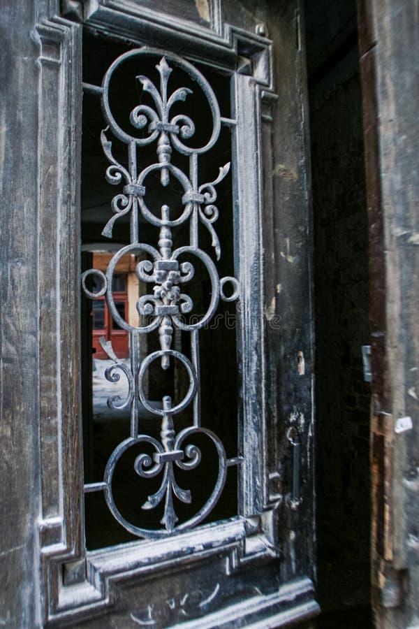 与木制框架的老铁鞋带门在城市议院里 免版税库存照片