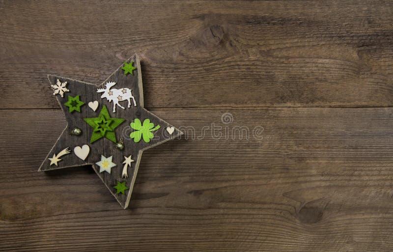 与木和绿色deco一个手工制造星的圣诞节背景  免版税库存照片