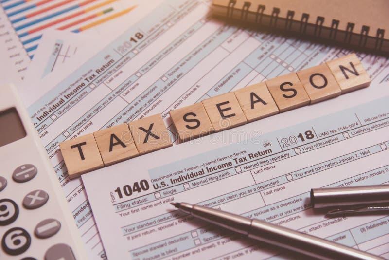 与木字母表块的税季节,计算器,在1040报税表背景的笔 库存图片