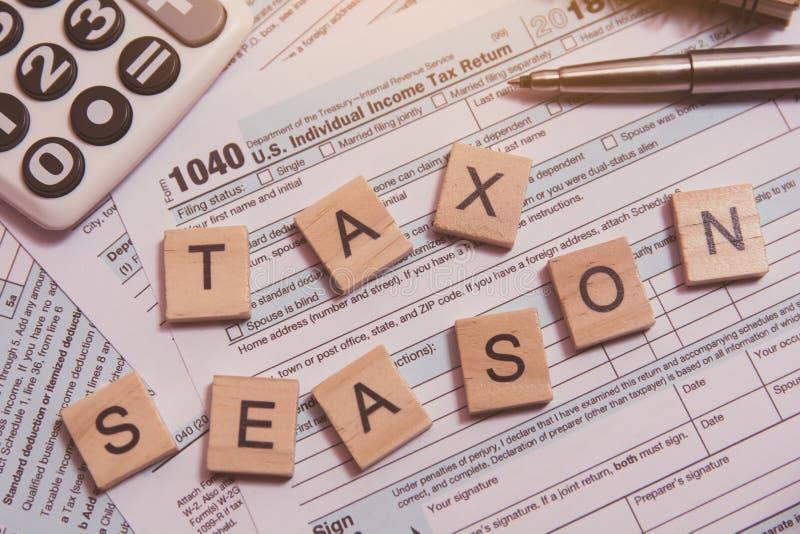 与木字母表块的税季节,计算器,在1040报税表背景的笔 图库摄影