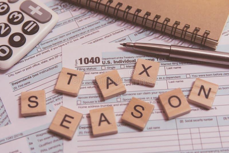 与木字母表块的税季节,计算器,在1040报税表背景的笔 免版税库存照片
