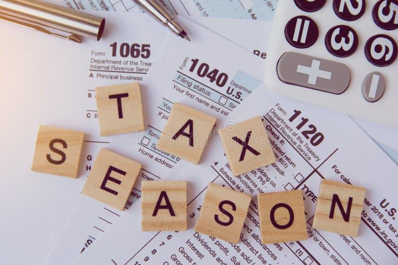 与木字母表块的税季节,计算器,在1040报税表背景的笔 免版税库存图片