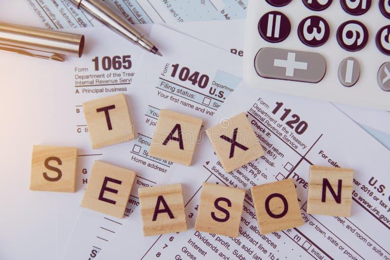 与木字母表块的税季节,计算器,在1040报税表背景的笔 库存照片