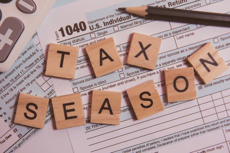 与木字母表块的税季节,计算器,在1040报税表背景的铅笔 图库摄影