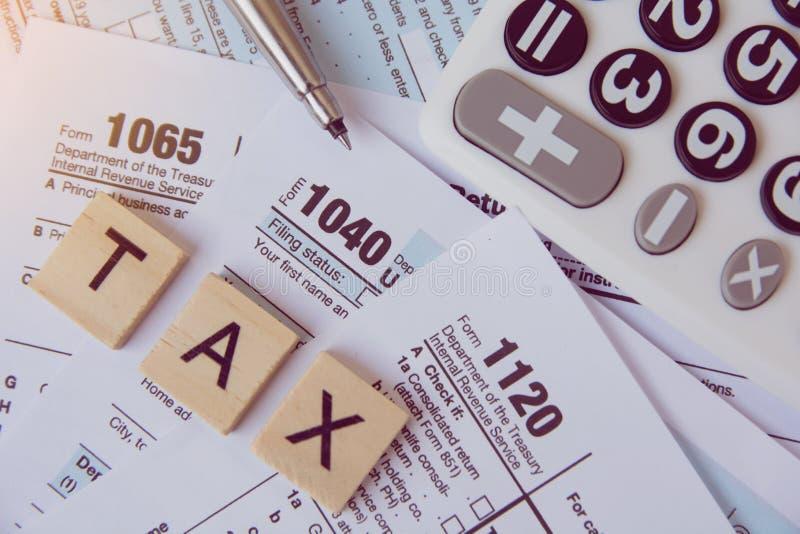 与木字母表块的税季节,计算器,在1040报税表backgrounda的笔 库存图片