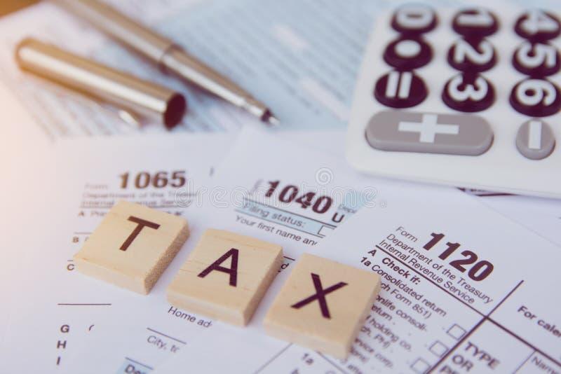 与木字母表块的税季节,计算器,在1040报税表backgrounda的笔 免版税库存照片