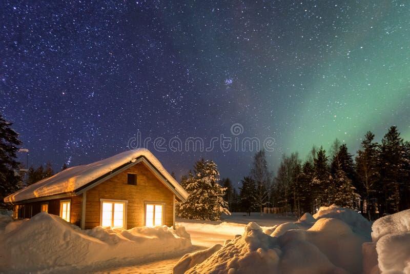 与木房子的冬天风景在美丽的满天星斗的天空下 免版税库存图片