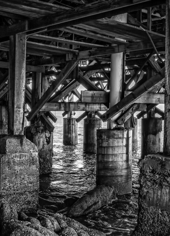 与木打桩和海的黑白纹理在码头下 免版税库存照片
