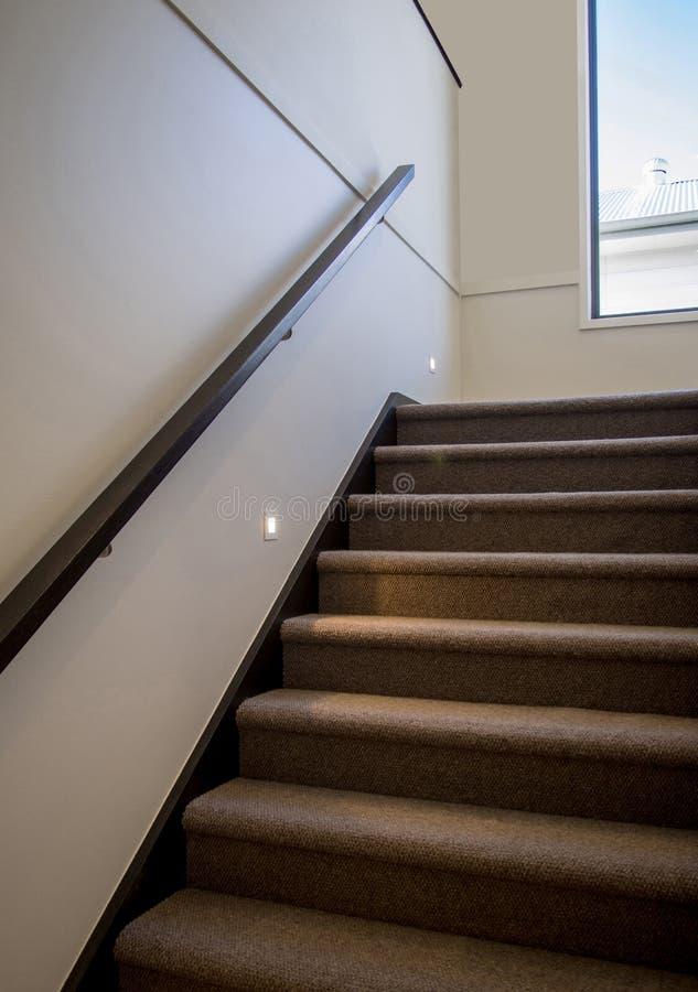 与木扶手和夜照明设备的现代覆盖着的楼梯 库存图片