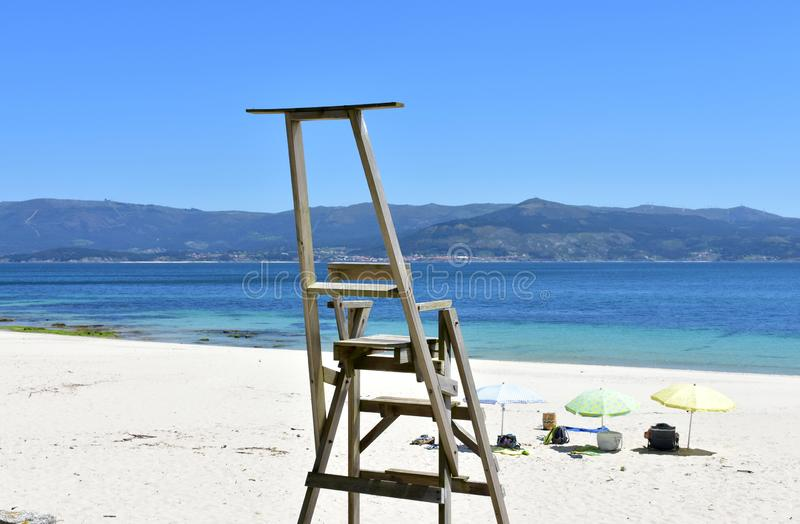 与木救生员椅子和沙滩伞的海滩 r 免版税库存照片