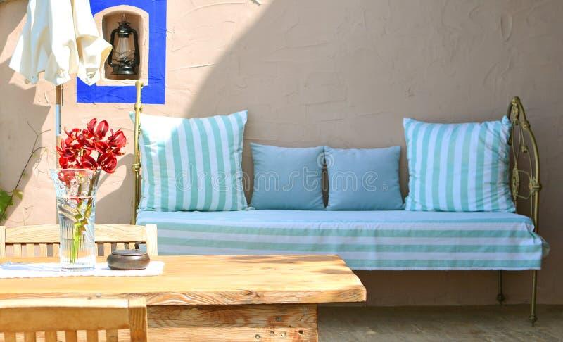 与木桌、椅子、花和沙发的地中海样式大阳台在背景 免版税图库摄影