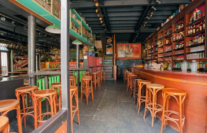 与木桌、瓶、饮料和五颜六色的装饰的空的酒吧 库存图片