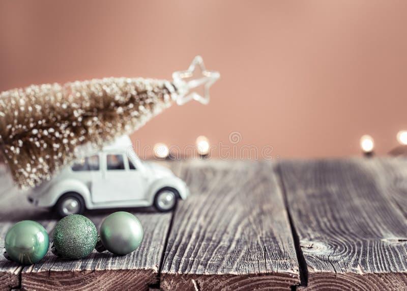 与木桌和小的VW玩具汽车运载的圣诞树的背景 库存照片