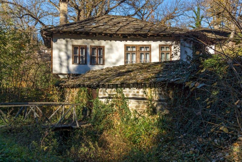 与木桥和老房子的秋天风景在Bozhentsi,保加利亚村庄  免版税库存图片