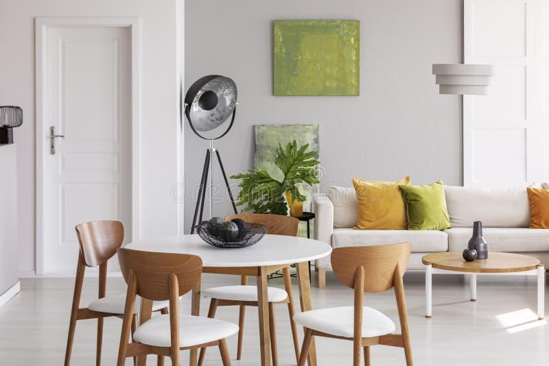 与木椅子的白色圆桌在有工业灯、舒适的长沙发和金黄石灰的时髦的客厅中间 库存照片