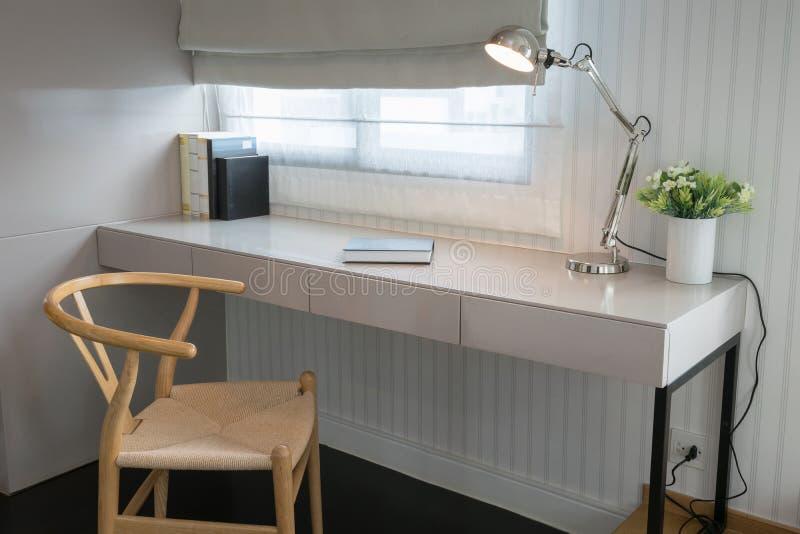 与木椅子的白色桌和书在现代操作范围 免版税图库摄影