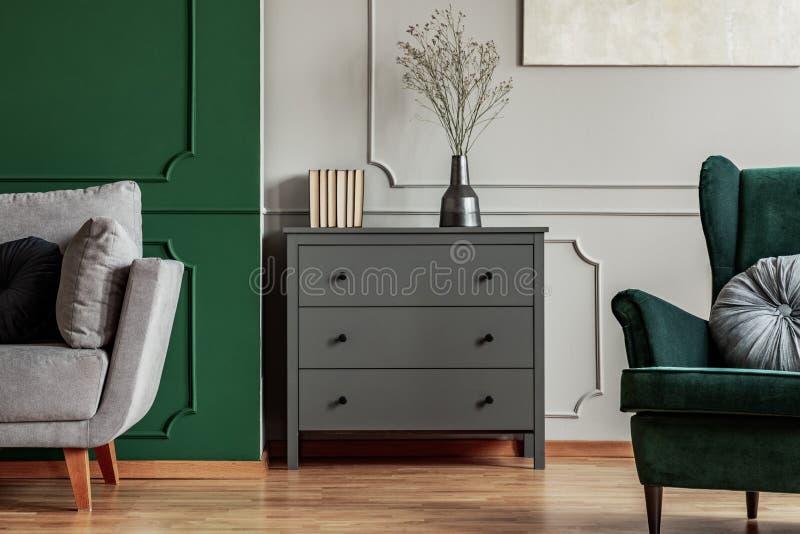 与木洗脸台、斯堪的纳维亚沙发和鲜绿色扶手椅子的时兴的客厅内部 库存照片