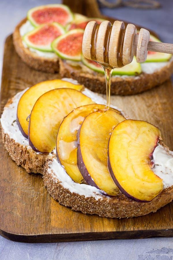 与木浸染工的倾吐的蜂蜜在与整个五谷麸皮黑麦面包切片的多士用乳脂干酪,桃子,无花果 免版税库存照片