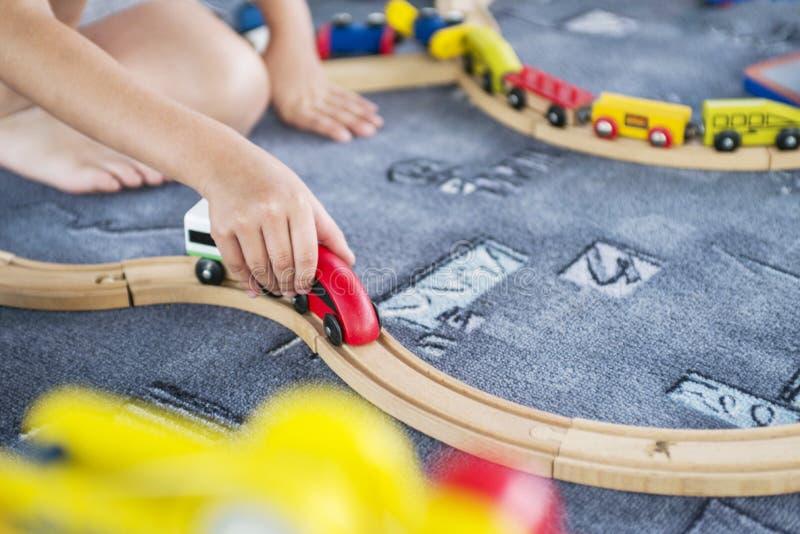 与木火车、修造玩具铁路在家或幼儿园的儿童游戏 小孩与木火车的孩子戏剧 免版税库存照片
