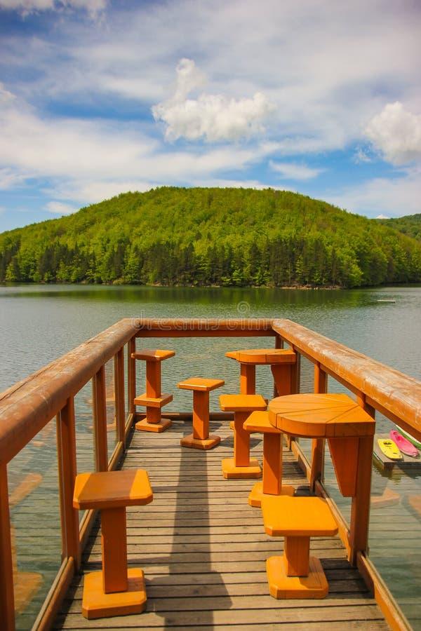 与木甲板的山风景有森林和桌的在湖Gozna围拢的椅子 免版税图库摄影