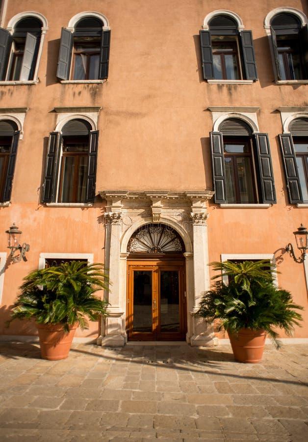 与木葡萄酒门的古老门面和Windows在威尼斯 免版税库存照片