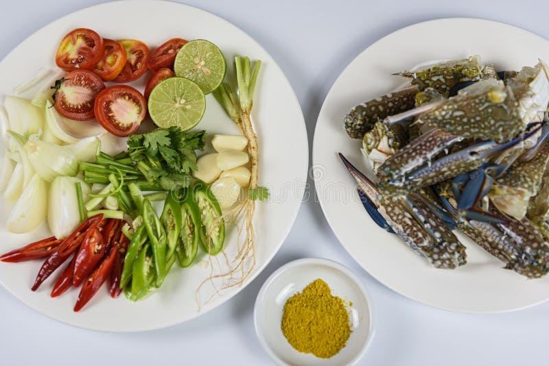 与未加工的螃蟹、柠檬、葱、胡椒、蕃茄、草本和香料的准备在白色板材,海鲜 免版税库存照片