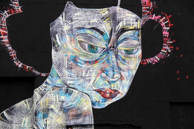 与未来派妇女` s面孔的面孔的印象深刻的街道艺术在黑墙壁,罗切斯特,纽约上的, 2017年 免版税库存图片