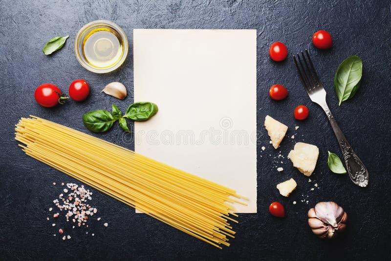 与未煮过的意粉的意大利食物背景、蕃茄、蓬蒿、乳酪、大蒜和橄榄油或者烹调面团在台式视图 免版税库存照片