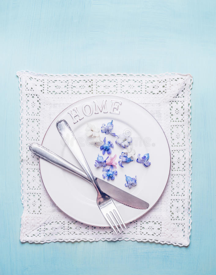 与本垒板、利器、鞋带小垫布餐巾和瓣的白色桌设置在蓝色破旧的别致的木背景开花 免版税库存图片