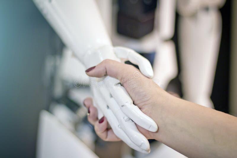 与机器人握手 妇女遇见一个机器人 库存照片