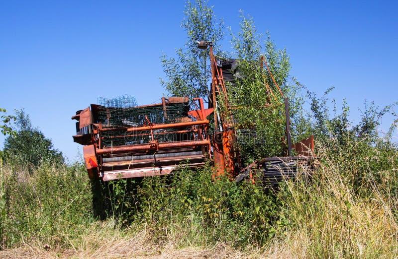 与杂草的红色红色生锈的农业机器等级在荷兰农厂agains天空蔚蓝 免版税库存照片