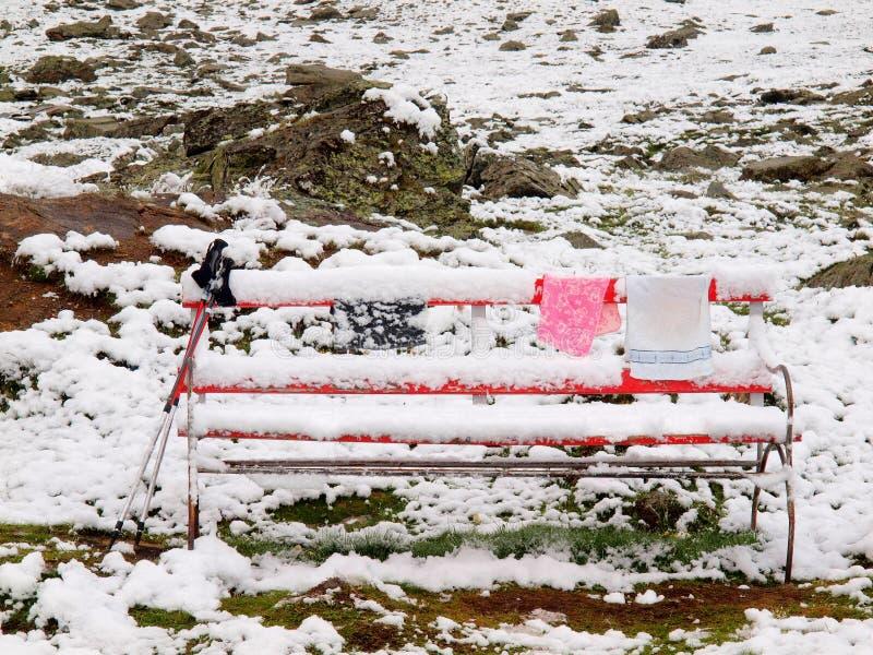 与杆和结冰衣裳的被放弃的红色多雪的长凳 免版税库存图片
