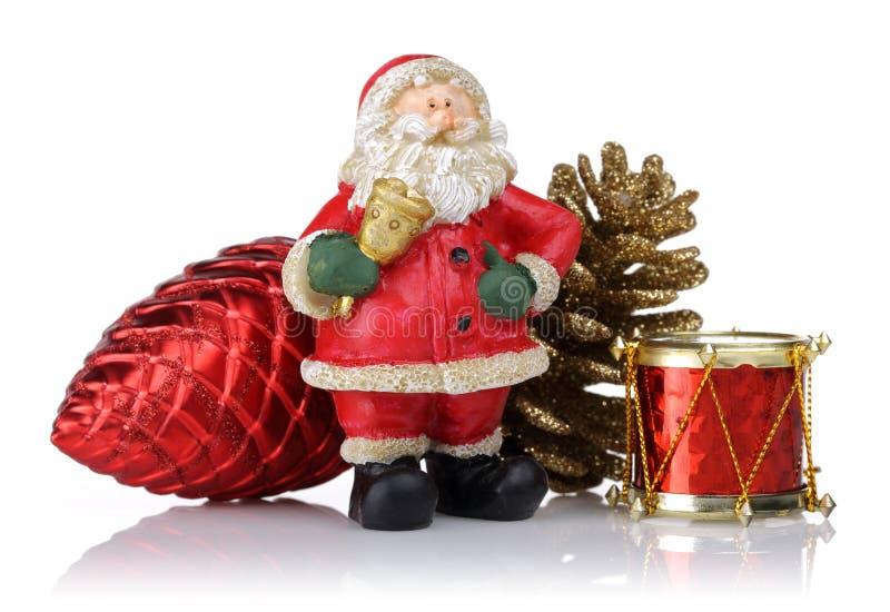 与杉木锥体和玩具鼓的圣诞老人 圣诞节查出的装饰品 免版税图库摄影