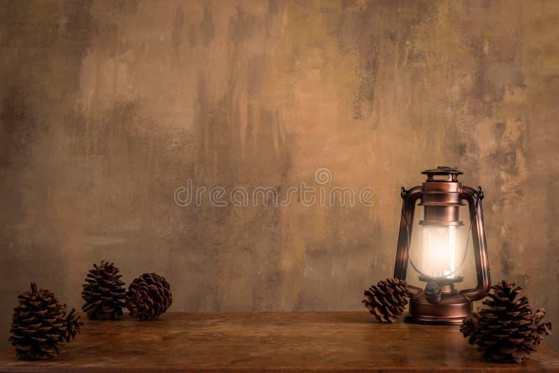 与杉木锥体的被点燃的古色古香的灯笼背景 图库摄影