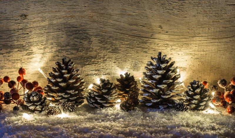 与杉木锥体,在雪的红色莓果的被阐明的自然土气圣诞节背景 免版税库存图片