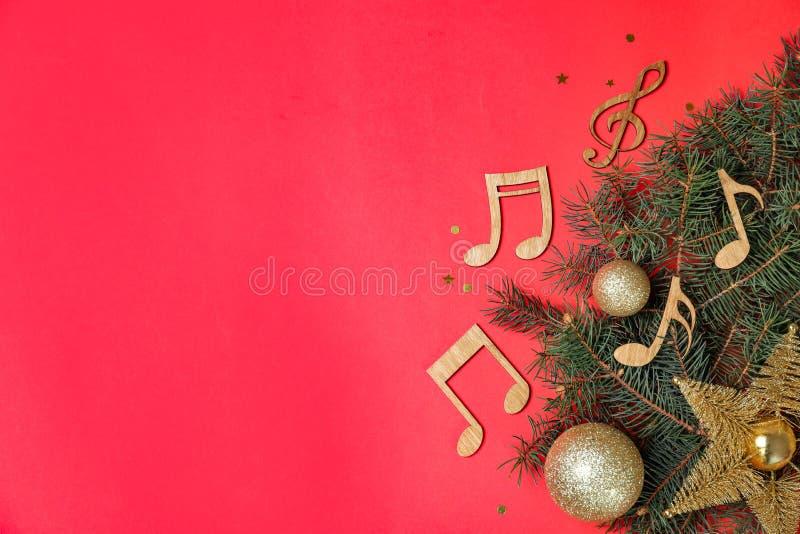 与杉树、圣诞节装饰和木音乐笔记的平的被放置的构成关于颜色背景 库存图片