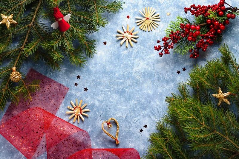 与杉树分支、红色丝带和装饰,木装饰品,五彩纸屑的圣诞卡片 圣诞节平的位置 库存照片