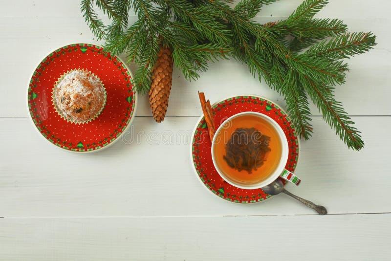 与杉树分支、锥体、圣诞装饰和杯子的圣诞节背景红色与两的果子热的茶 免版税图库摄影