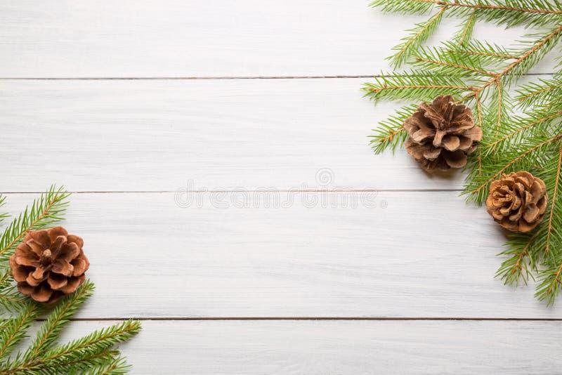 与杉树分支和锥体的圣诞节白色木背景 与拷贝空间的顶视图您的文本的 免版税库存图片